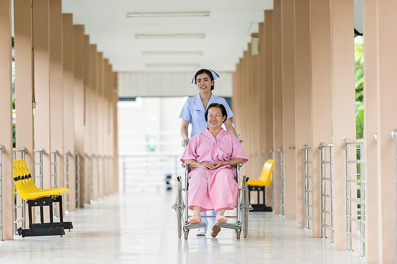 Senior women on a wheelchair is assisted by a nurse